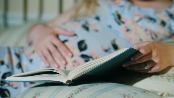 Těhotná žena čte knížku v posteli