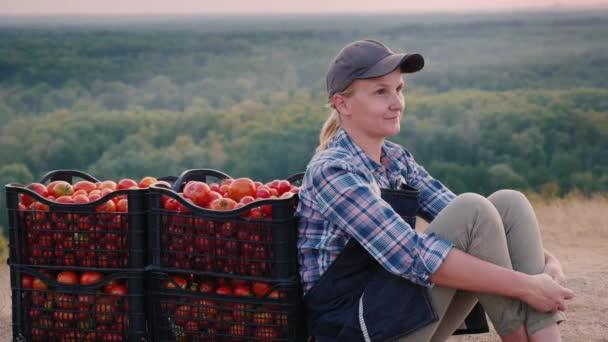Žena farmář odpočívá po sklizni rajčat