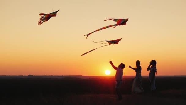 I bambini con mamma giocano un aquilone al tramonto in una serata estiva. Genitori attivi e bambini