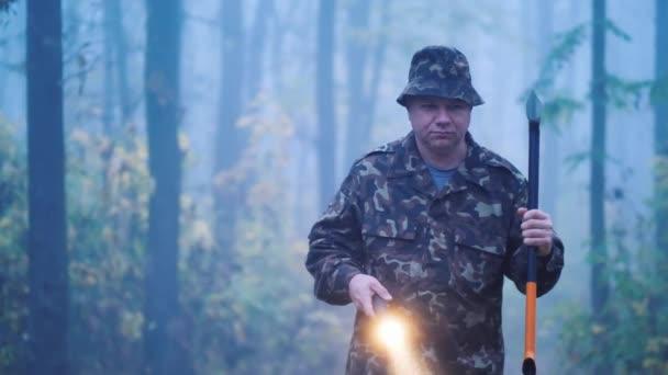 Brutális ember fejszével és zseblámpával sétál az erdőben.