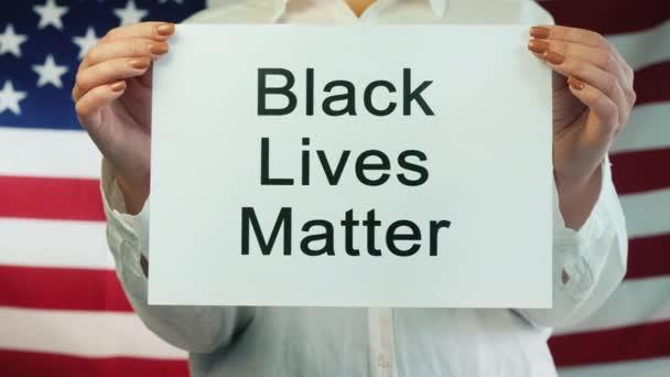Žena drží plakát Black Lives záležitost na americkém vlajkovém pozadí