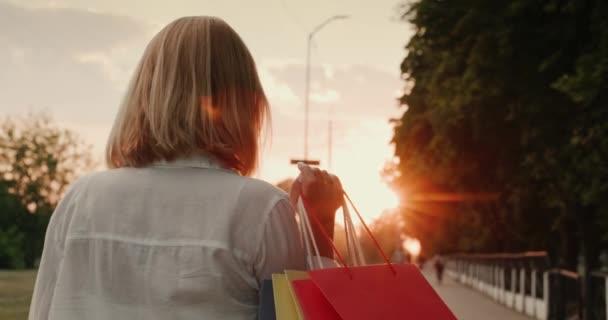 Spokojenost ženského nakupujícího nese balíčky s módními nákupy