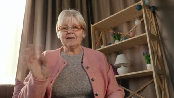 Starší žena komunikuje přes video link, pohled z notebooku