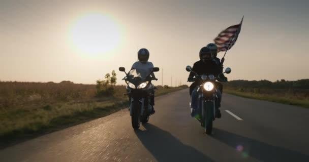 Skupina cyklistů jezdí po dálnici při západu slunce, s vlajkou Ameriky cestuje po celé zemi