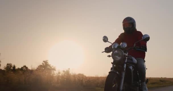 Motorkářská jízda na venkovské silnici při západu slunce