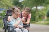 Egy fiatal lány, segítve a kerekesszék fogyatékkal élő nővére
