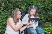 A fogyatékos gyermek a kerekesszékben lét gondozni, egy önkéntes gondozó-ápoló.