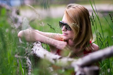 young blonde girl on nature background in summer close-up