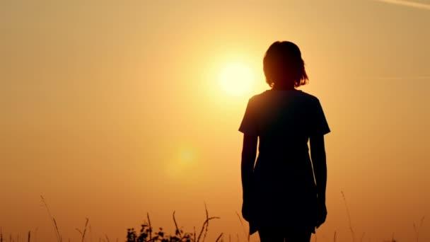 Zpomalený pohyb silueta šťastnému páru. Chlap je objímat dívku před západem slunce. Milující muž a žena