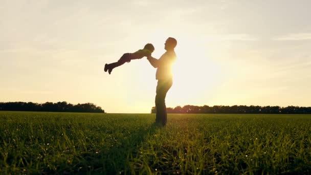 glücklicher Vater und Sohn beim Naturspielen im Park bei Sonnenuntergang. Der Vater hält seinen Sohn an der Hand und dreht sich mit ihm um. Zeitlupe.