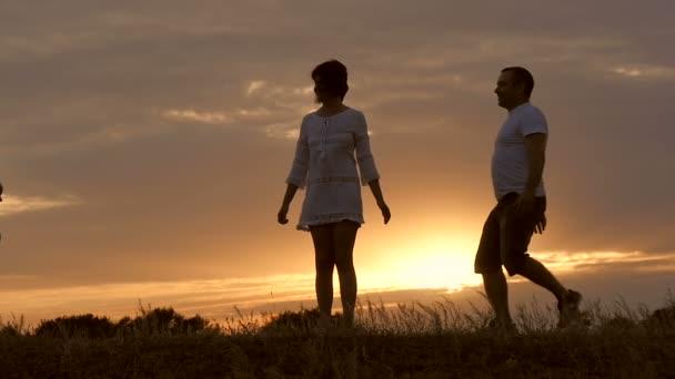 Silueta šťastné rodiny. Tati, dvě děti jsou objímání moje matka při západu slunce. Koncept šťastné rodiny