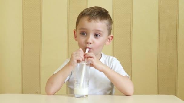 Šťastné dítě pije mléko ze sklenice brčkem, potěšení a palce ruky.