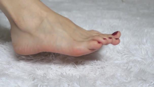 Nohy mladá žena close-up na bílém pozadí. Pojetí krásy a zdraví.