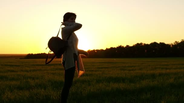 Slowed movement of a girl dressing a backpack and walking along a green lawn against a sunset background