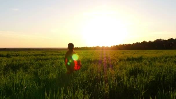 Un bambino in un costume da supereroe in un mantello rosso corre attraverso il prato verde sullo sfondo del tramonto