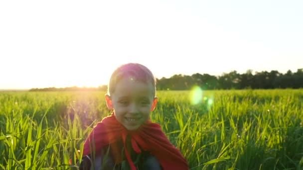 Un bambino felice in un costume da supereroe in un mantello rosso si siede su un prato verde contro il tramonto e poi sale