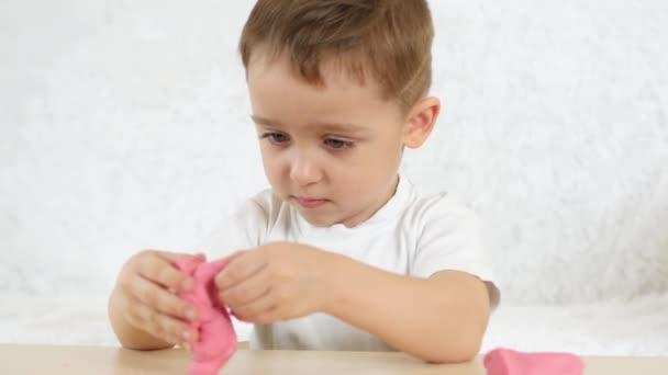 Dětské tvořivosti. Dítě s radostí tvoří tvary z barevných testu na stole na bílém pozadí. Roztomilé dětské Plastelíny figurky na stůl