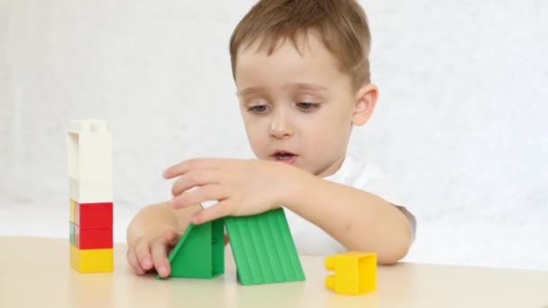 A child is playing with colored blocks, building a house, sitting at a table on a white background. Child and toys. 4k