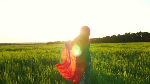 Un bambino felice in un costume da supereroe in un impermeabile rosso corre lungo un prato verde contro il tramonto, guardando indietro
