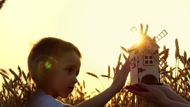 Happy kid playing with a small wooden windmill at sunset. Wheat field. The concept of agriculture and harvesting.