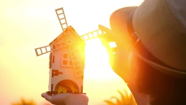 Egy lány áll egy területen napraforgó, és tart egy játékszer szélmalom a háttérben ellen a naplementét. A malom kiderül, a lány kezében. A koncepció a betakarítás.