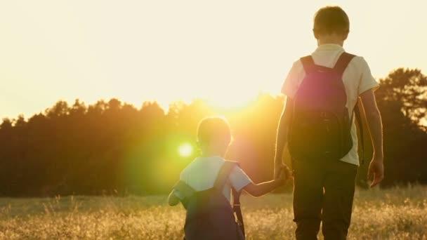 Két testvér, egy turista hátizsákok, séta a gazdaságot, hogy a háttérben a naplemente, a lassú mozgás. Boldog gyermekek séta a természetben