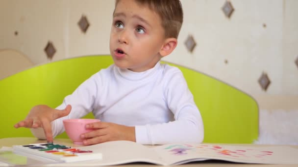 Happy child paints with watercolors while sitting at the table. The little boy puts his finger in the paint and smears the picture on a sheet of paper. The development of a child of preschool age.