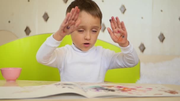 A naughty boy takes paint and claps his palms on the paper. Development, education, psychology, emotions of a child.