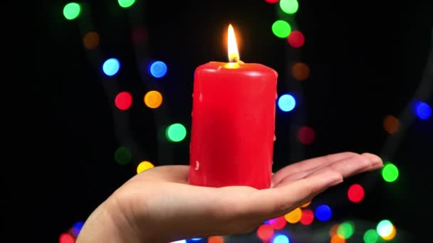 Close-up of female hand with a big red candle on bokeh background. Burning candle on a black background. Religion, spirituality and celebration.