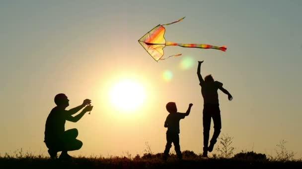 Silhouette einer glücklichen Familie bei Sonnenuntergang. Papa und zwei Kinder spielen mit einem Drachen in der Natur