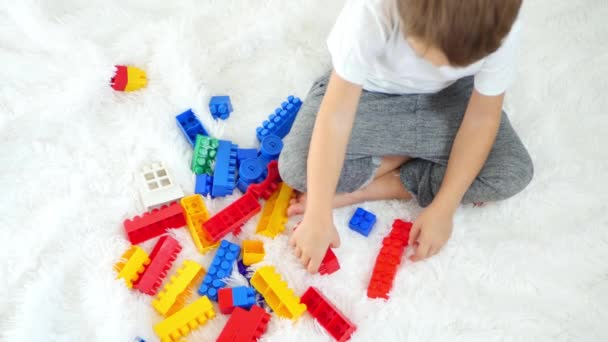 A child is playing with color blocks on a white background. The concept of child development.