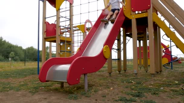 The child rides on the playground from top to bottom. Slow motion.