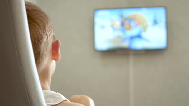 The child is watching a cartoon. The TV screen is out of focus.