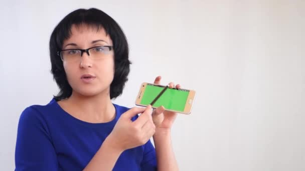 Brunette girl demonstrates the green screen of the smartphone on a white background. Girl businessman tells the information, showing the screen of the smartphone.