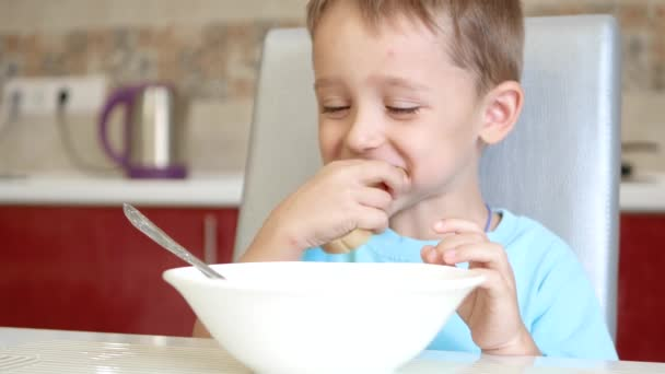 The child sits at the kitchen table, eats bread and soup. The concept of healthy baby food.