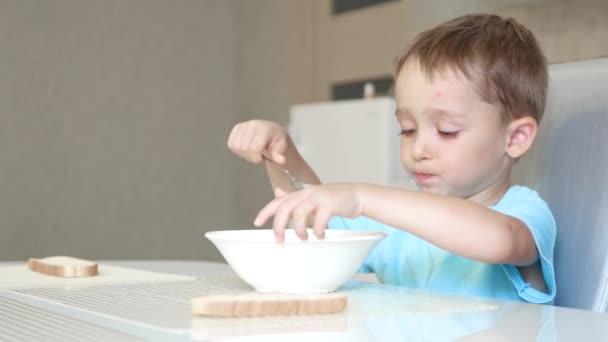Dítě sedí u kuchyňského stolu a jí polévka s chlebem s radostí. Pojem zdravé dětské výživy.