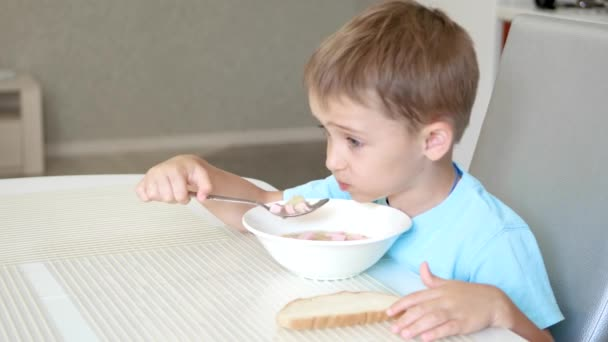 The child sits at the kitchen table and eats sausage soup. The concept of healthy baby food.