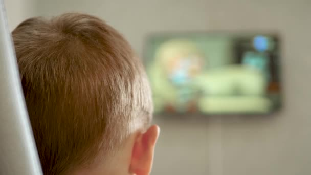 A child is watching a cartoon sitting on a chair. The TV screen is out of focus.
