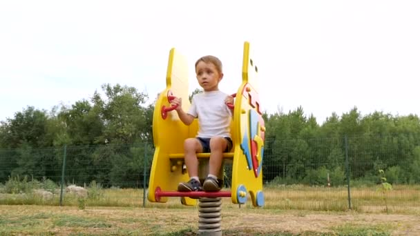 A happy child is on the playground, swinging on a yellow swing.