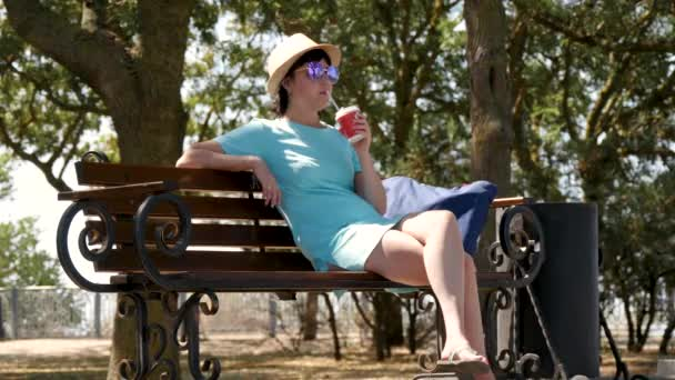 A brunette girl in a hat and dress is sitting on a park bench and drinking coffee.