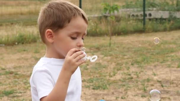 Happy baby blowing soap bubbles. Bubbles fly in the wind in slow motion, close-up.