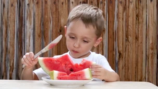 das Kind sitzt am Tisch vor einer Holzwand und isst mit einem Messer eine Wassermelone.