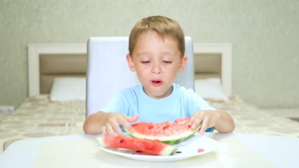 glückliches Kind sitzt am Tisch und isst mit Vergnügen Wassermelone.