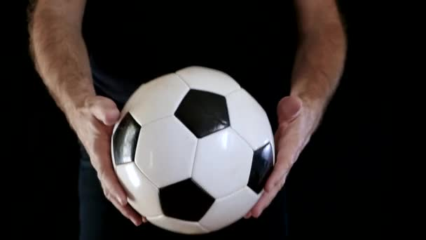 A man-athlete plays with a soccer ball, throwing it. A man on a black background. Close-up.