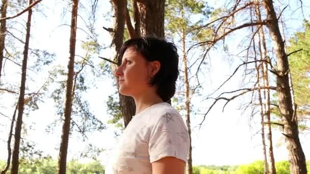 Eine junge Frau im Wald blickt nachdenklich in den Sonnenuntergang. Bewegen Sie die Kamera um das Mädchen.
