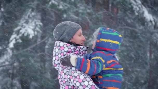 A happy mother kisses her child against the backdrop of a winter forest. Two people on a snowy day in winter.