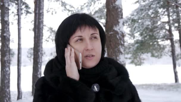 Detail bruneta žena stojící proti lesa nebo parku na zimní den. Dívka se drží její smartphone a mluví. Pohyb kamery steadicam.