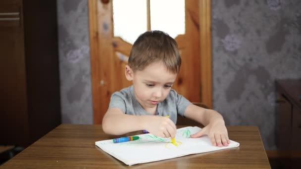 A mosolygó gyermek óvodáskortól ül egy asztalnál otthon és felhívja fényes színes ceruza vagy kréta papíron. A kreativitás és a gyermekek.