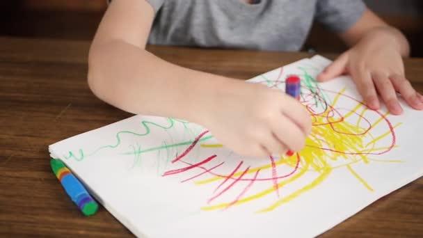 Közeli kép: egy kis gyerek, rajz élénk színű ceruzák vagy ceruzával papírra ülve, egy fából készült asztal. Gyermekjáték az óvodáskortól, kreativitás fejlesztése.