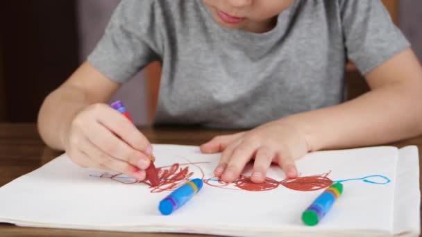 Ismeretlen gyermek támaszkodva fényes színes ceruza a fehér könyv az asztalnál ülve. A koncepció a fejlesztés és az oktatás, a gyermekek.
